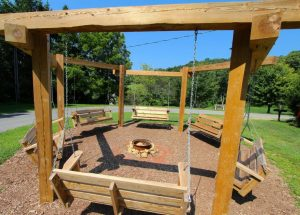 A firepit with porch swings mounted in a circle around it.